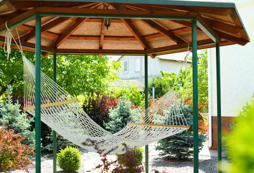 Beautiful English style garden with comfortable hammock on sunny day