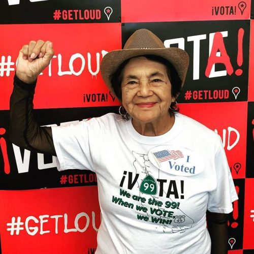 Dolores Huerta in a tan hat wearing a shirt that says I VOTED We are the 99 When we vote we win! Vota Get Loud!