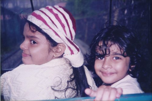 Aarya with her sister as children. Aarya has short curly dark hair and bangs, and her sister is wearing a red, pink, and white striped head kerchief and a white sweater. They're looking at the camera over their shoulders and are heckin cute.