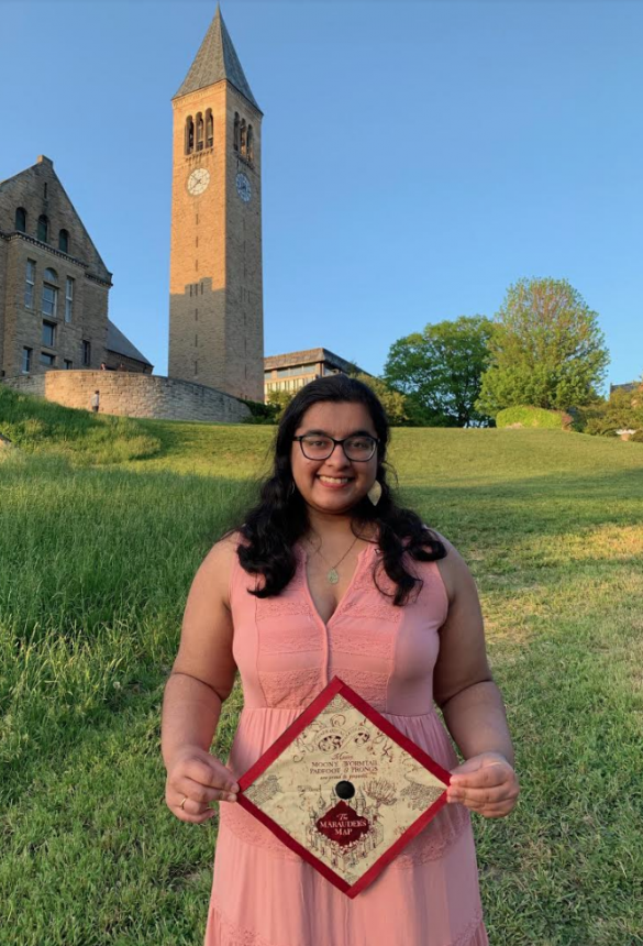 Aarya holding her mortar board from graduation which has a picture of the Marauder's Map from Harry Potter on the top. She's wearing a pink dress and standing in front of the tower on her campus.