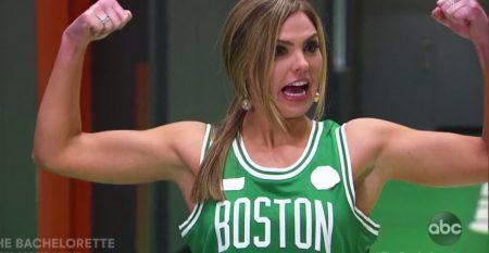 Hannah flexes her biceps while wearing a Celtic's jersey