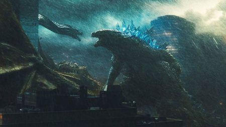 Godzilla and King Ghidorah fight during a storm. There's a cityscape behind them
