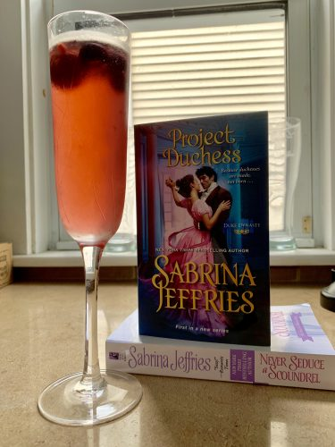 A pink sangria with fruit in a fluted glass next to a stack of books.