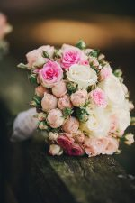 Wedding bouquet of pink and white on a dark wood background Photo by Andriy Medvediuk