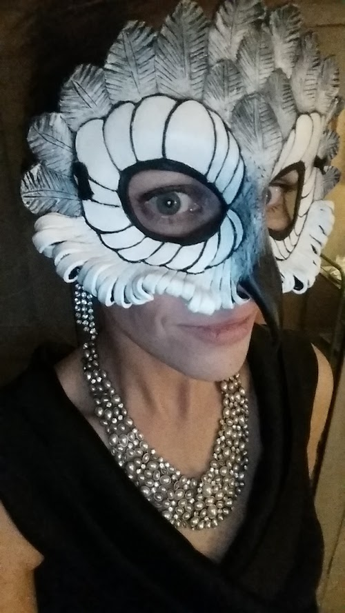 Charlotte B wearing a white owl mask and a gorgeous necklace with a black vneck top