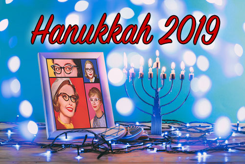 A framed picture of the original ladies on atable with blue lights and a menorah beneath the words Hanukkah 2019