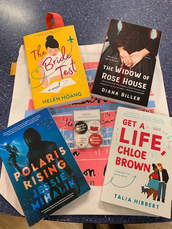 A picture of The Bride Test, Polaris Rising, Get a Life Chloe Brown, an Widow of Rose House on top of a printed tote bag and with a set of four button magnets on a blue countertop