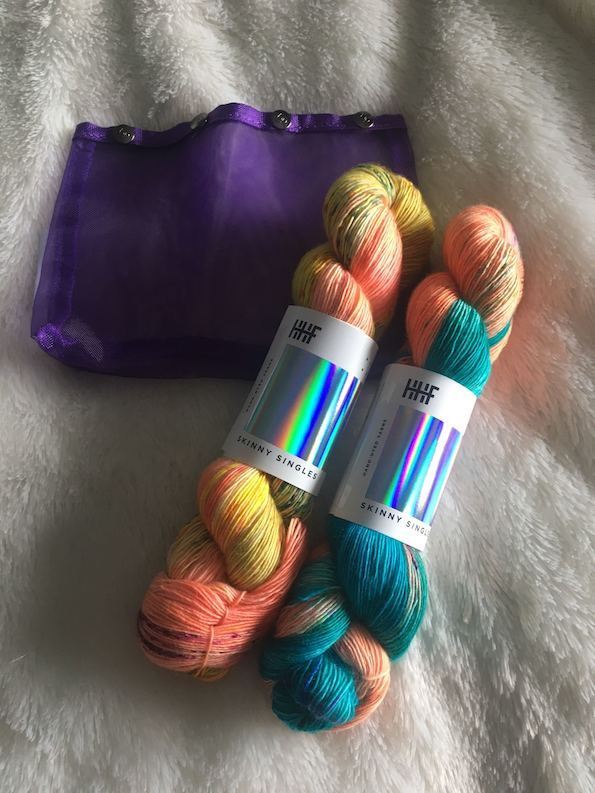 two skeins of teal and gold and coral yarn and a purple yarn tote against a fluffy background