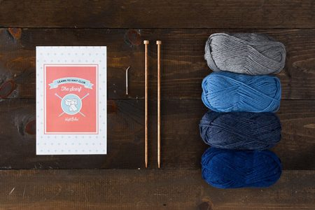 Knitting needles, four skeins of yarn and a book against a wooden backdrop