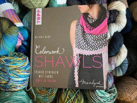 Melanie Berg's book Colorwork Shawls sits on top of a pile of yarn
