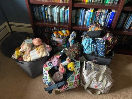 Five totes filled with yarn sitting in front of my bookcase
