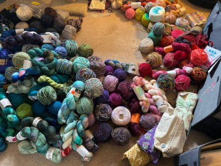 Many, many skeins of yarn form a half circle of my floor. They're lumped into piles by color