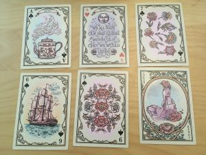 six of the cards as examples of the art: teapot, quotation, flowers, sailing ship, flowers, woman looking into distance