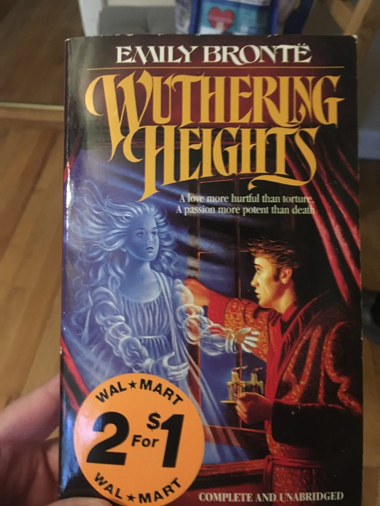 An old copy of Wuthering Heights. A man is wearing a luxe red housecoat as a ghost woman stares at from behind a window.