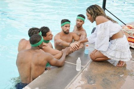 Tayshia crouches by the side of the pool and talks to the green team