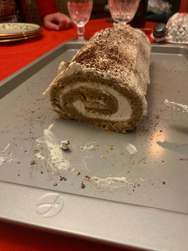 Spice Cake Swiss roll covered and filled with brown sugar whipped cream with cocoa powder on top