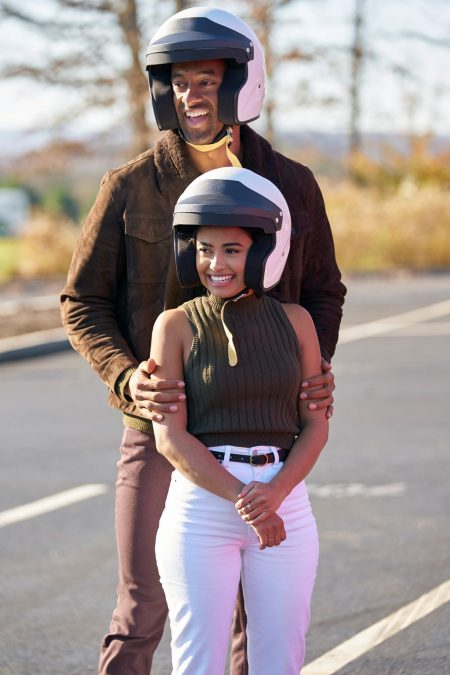 Jessenia and Matt stand next to each other wearing racing helmets