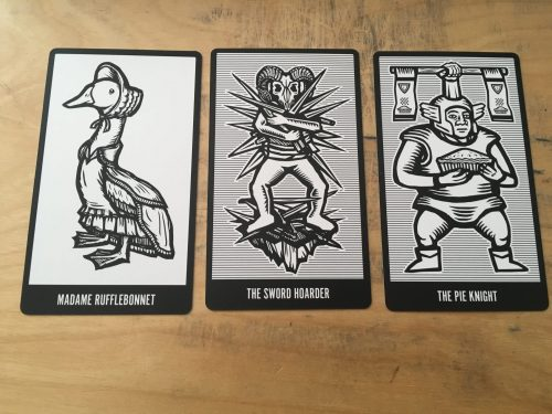 three black and white cards, Madame Rufflebonnet, a goose wearing a bonnet, The Sword Hoarder, who has a ram skull head and is in fact hoarding swords, and The Pie Knight who is a knight holding a pie