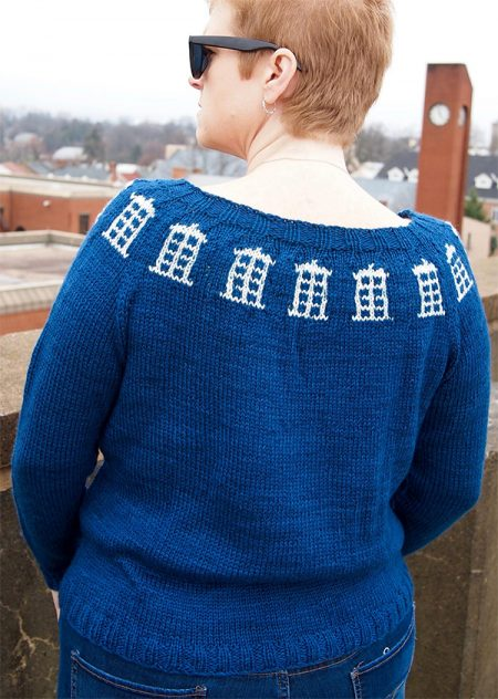 A woman models a blue sweater with tardises around the cowl in white