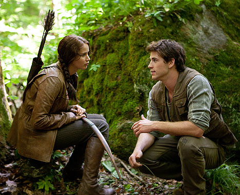 A scene from the Hunger Games film, with saturated green and sunlight framing the actors.