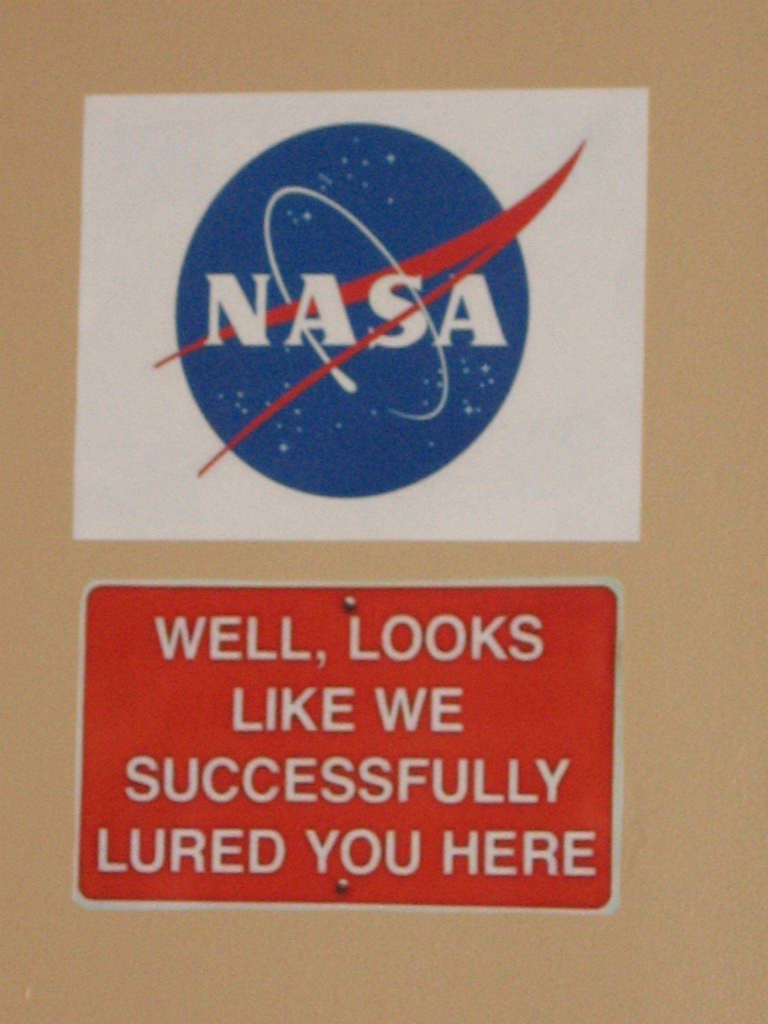 NASA symbol with sign beneath that reads Well, looks like we successfully lured you here.