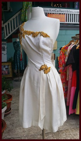 white one shouldered dress with gold trim, on a model dummy outside a shop
