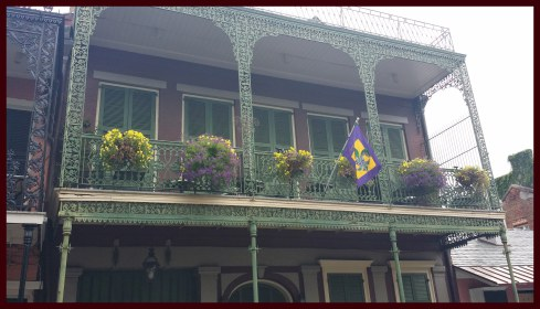 French Quarter wrought iron balcony with window pots, plants and flowers in purple and yellow