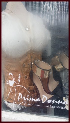 A leather steampunk corset and matching shoes in a shop window