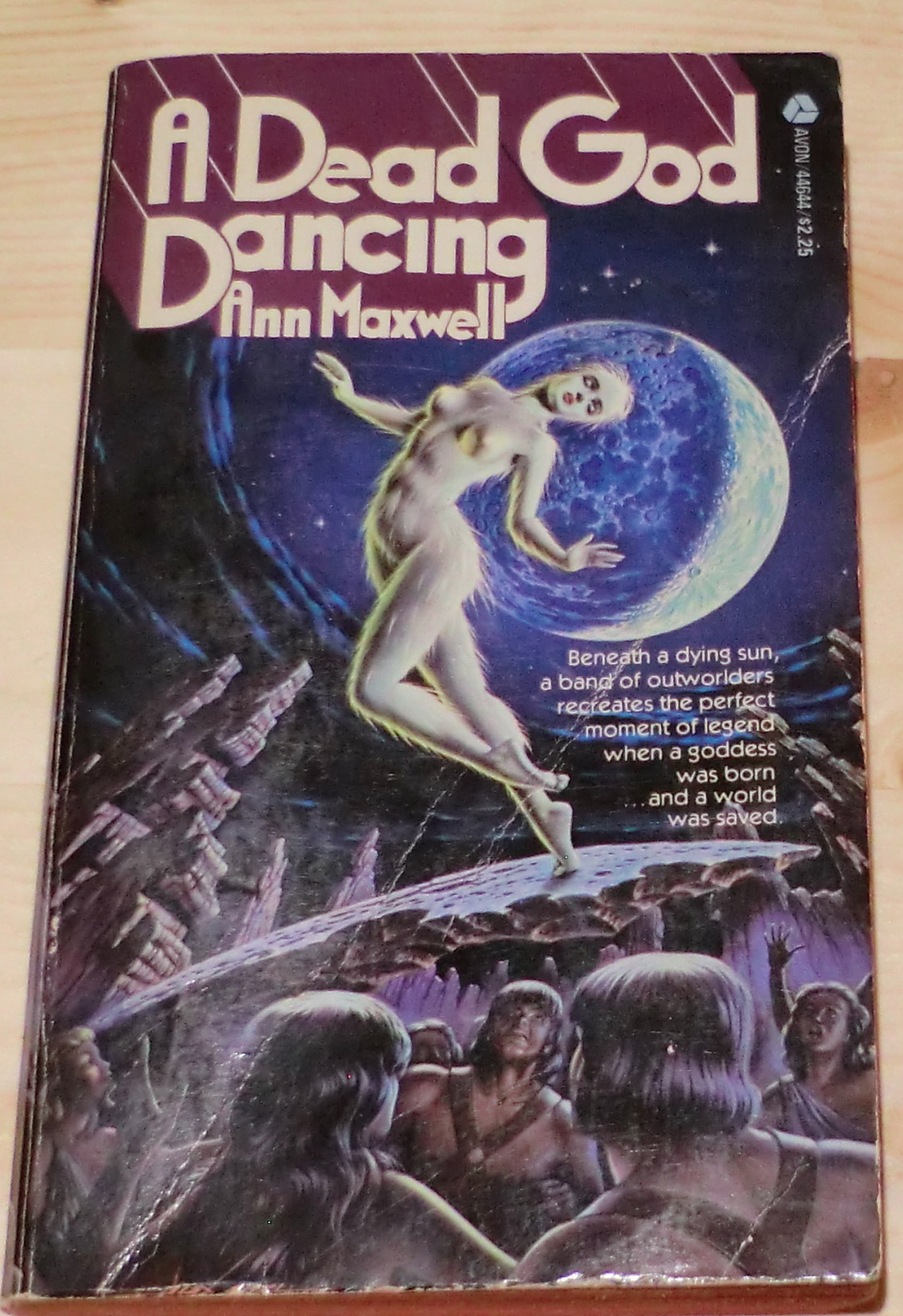 A dead god dancing - a pale white woman who looks like she's naked and covered with feathers dancing above a group of long haired angry primitive-looking men