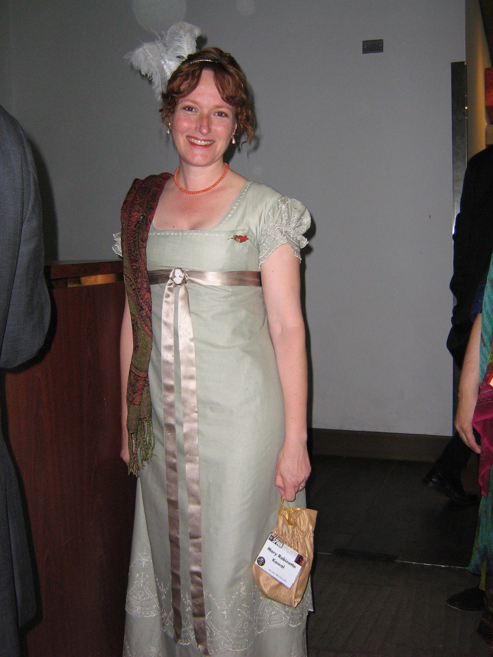 Mary Robinette Kowal in a hand-sewn Regency garment she made herself it is a pale grey with detailed lace gathered at the sleeves