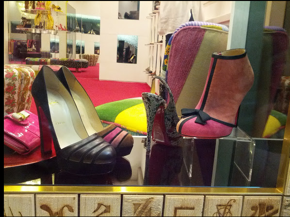 Christian Louboutin shoes in a shop window. One pair is an ankle bootie that is pink and red suede in huge blocks over the front of the shoe. Really beautiful.