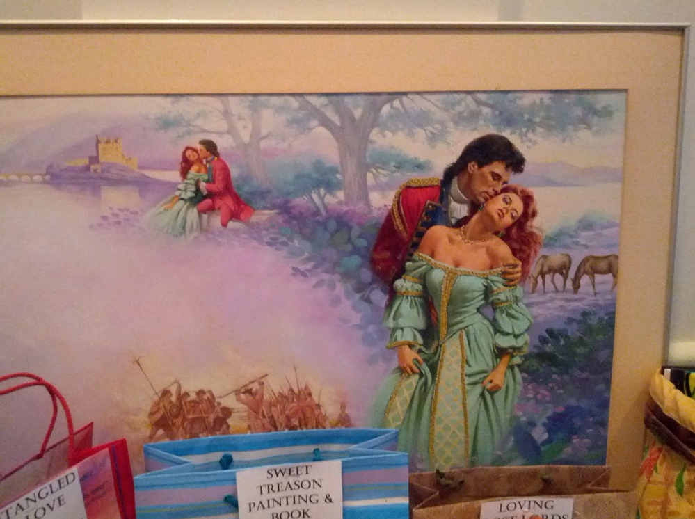 Sweet treason cover art framed - turquoise dress against a purple background with a guy with a mullet - and I think he's eating her ear.