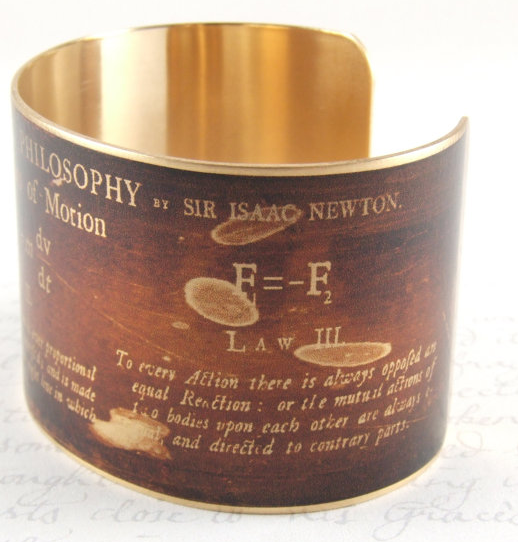 A burnt brown metal cuff bracelet with Newton's mathematical laws of motion printed in gold. It's badass.