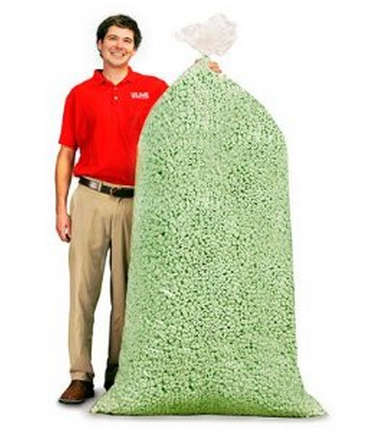 A guy in a red polo shirt standing next to a 5 foot tall bag of packing peanuts.