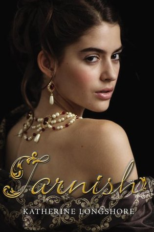 A woman with dark eyes and dark eyebrows and hair looking over her bare shoulder at the reader, with a very ornate necklace going down her back