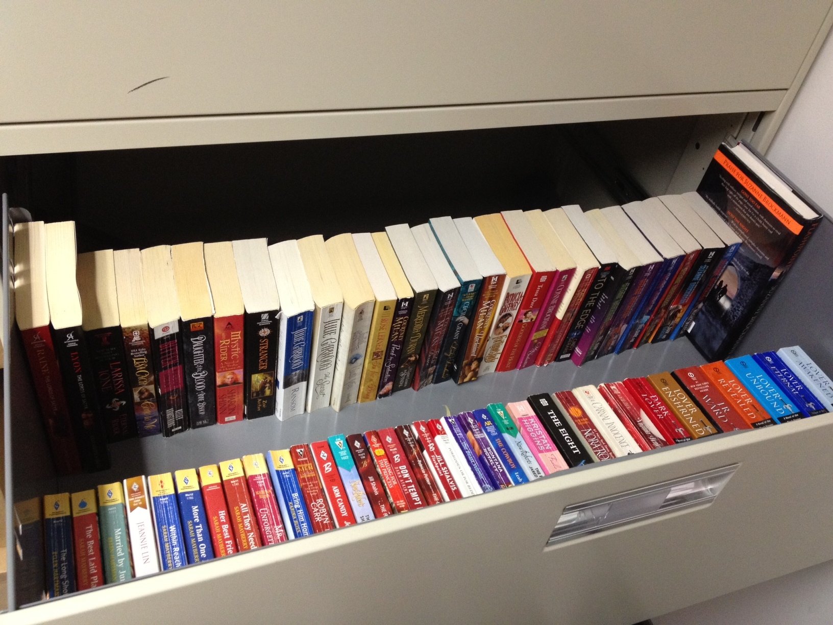 A long desk drawer FILLED with romance novels lined up in order.