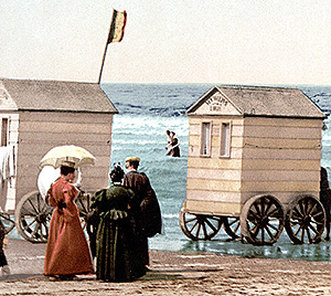 Women outside a bathing box a small shed on wheels with high frosted windows that is rolled into the surf