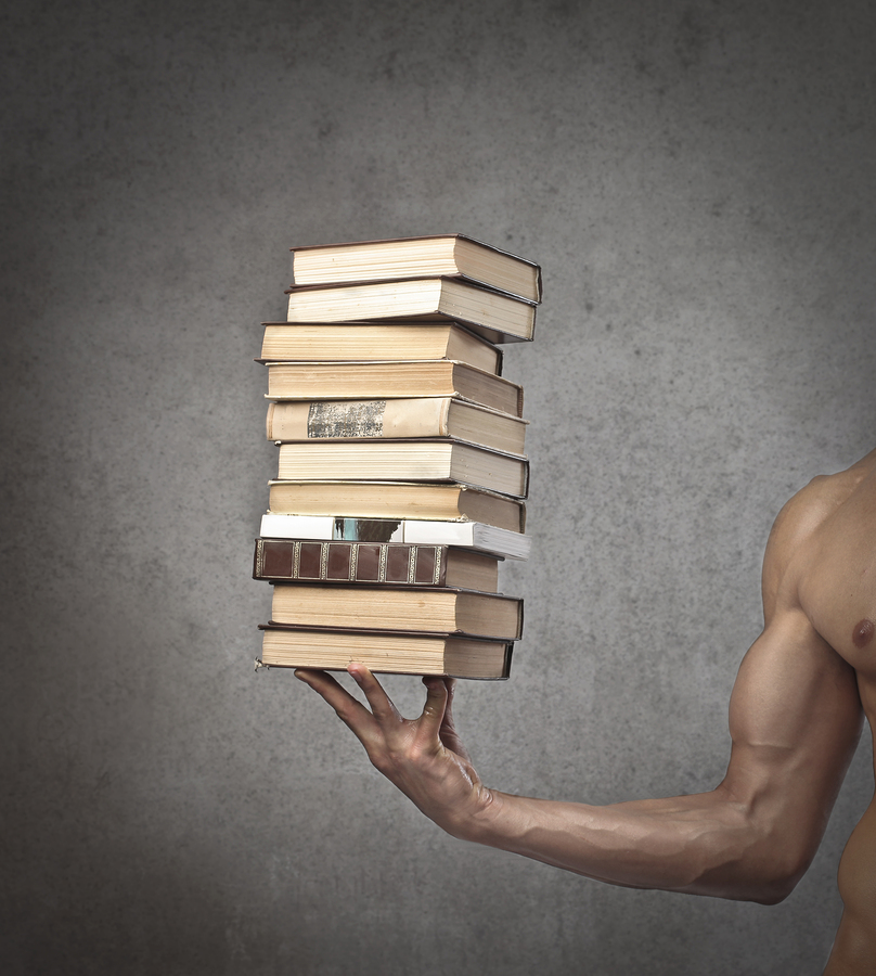 burly bicep holding stack of books