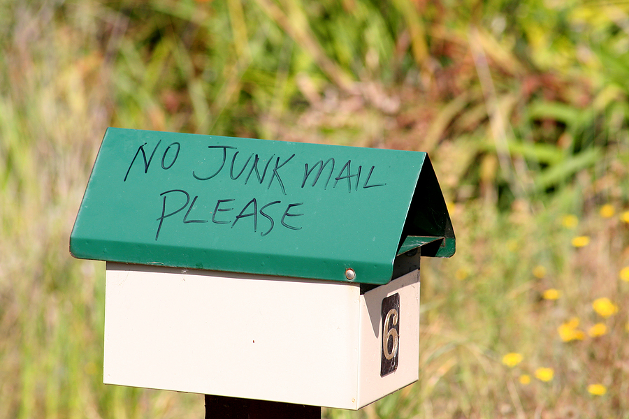 A roadside mailbox with a green roof, with