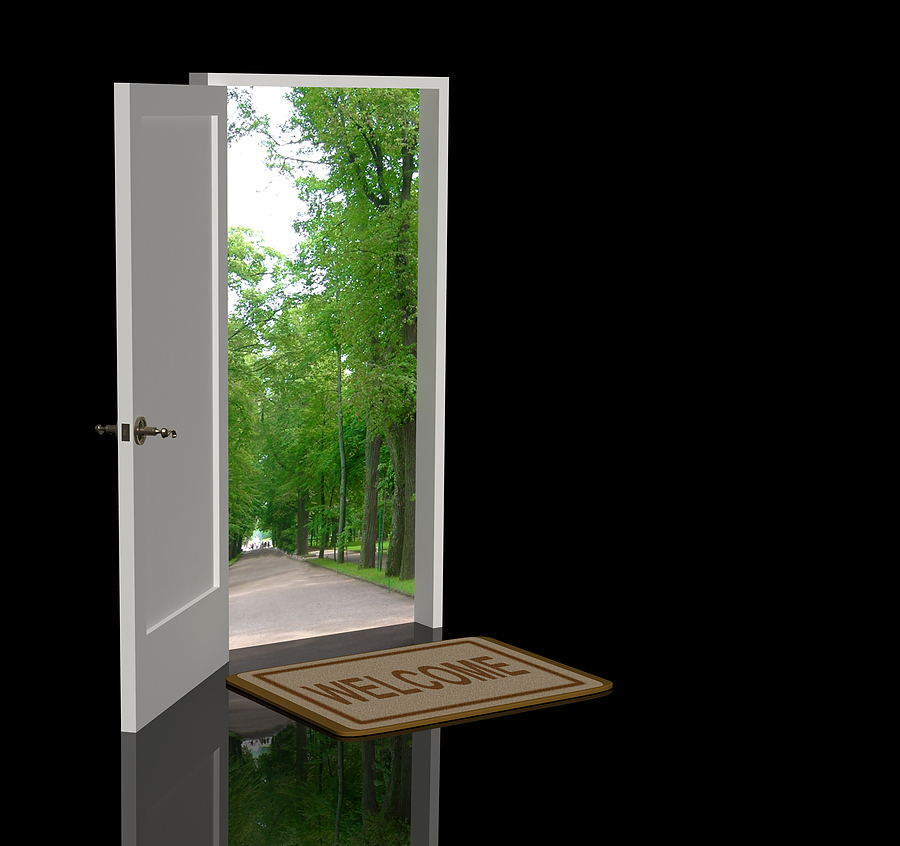 open door in black room leading to green path in a park