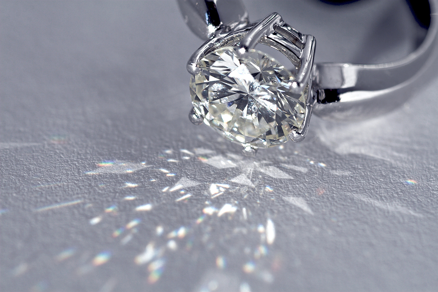 a close up of a diamond reflecting light against a grey surface