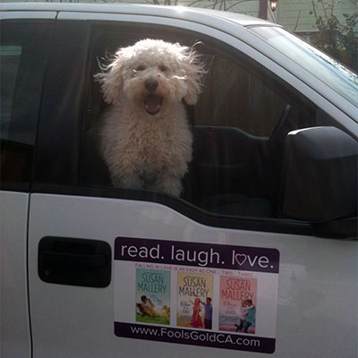 A very happy white fuzzy dog looking out a car window with a Susan Mallery magnet on the door.