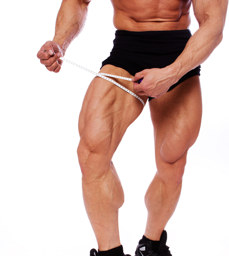 A very muscular man using a tape to measure the circumference of his absolutely massive thighs - image from Shutterstock